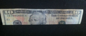 Picture of a ten dollar bill folded lengthwise.