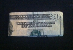 Picture of a twenty dollar bill folded in half and again lengthwise.