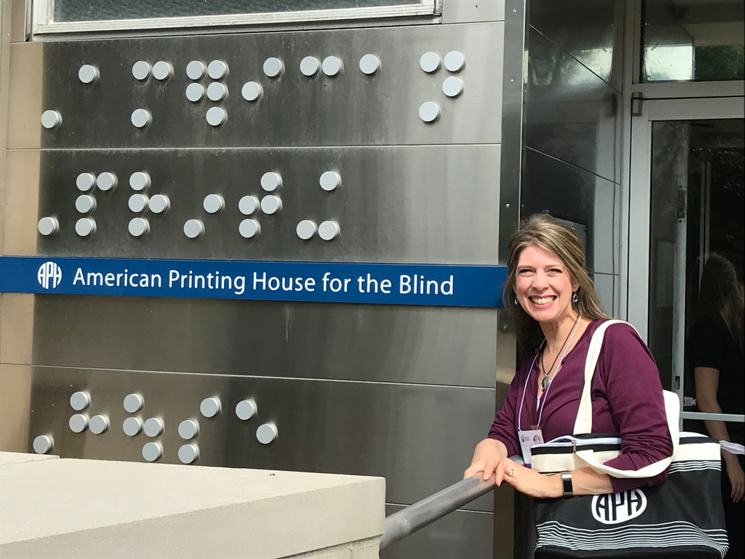 Carmen Willings posing beside the entrance to the American Printing House for the Blind