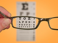 Picture of glasses directed at an eye chart.