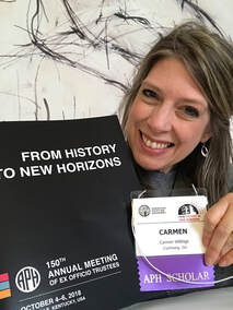 Image of Carmen Willings holding 150th Annual Meeting Agenda and APH Scholar namebadge